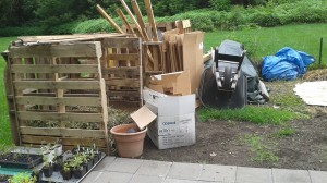"All of the building supplies, tools, and other garden miscellanea are carefully piled in one end of the garden, next to the compost bins. This is an attempt to minimize the perceived messiness of the garden and avoid accusations of looking ""hillbilly."""